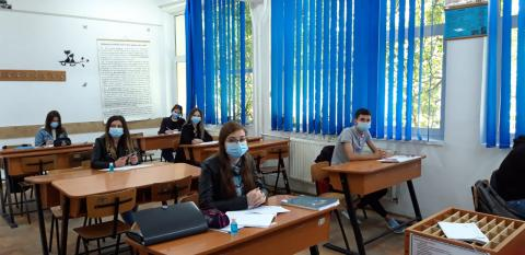Students sitting in class, masks on, to prepare for exams