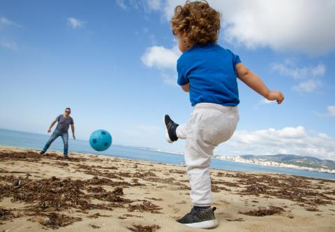 A child plays football with his father at the beach