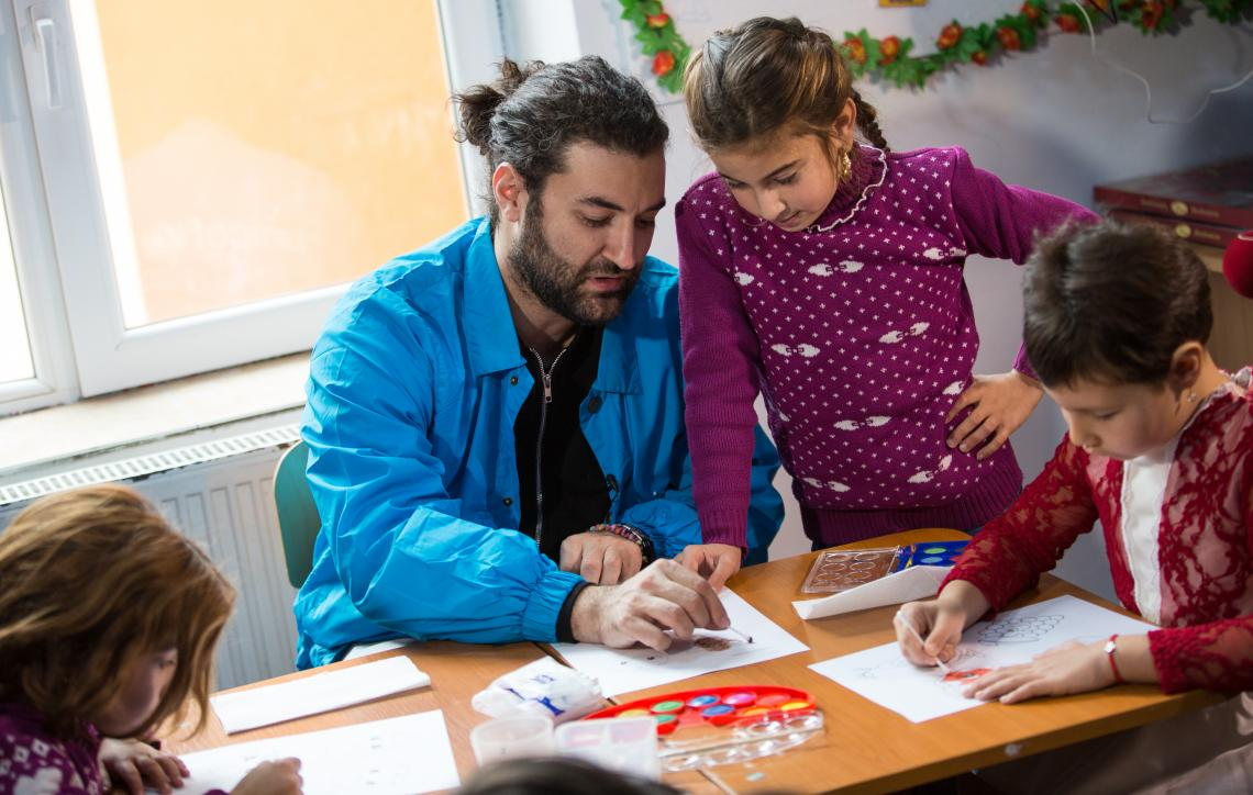 Smiley, National Ambassador for UNICEF in Romania, visiting the Orbic community where UNICEF implements Quality Inclusive Education Package. One of the children helps him draw.