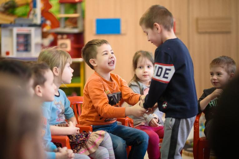 "Little boy shaking hands with all his kindergarten colleagues as a part of a daily icebreaker exercise in ""Dumbrava Minunata"" kindergarten, Bacau, Romania, 2020"