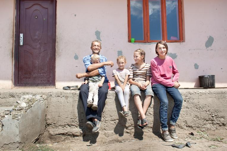 Father with children in front of the house, Romania