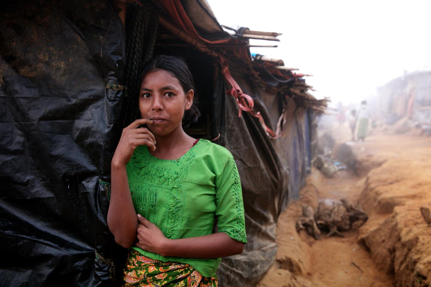 On 19 December 2017 in Bangladesh, Noor Bar, 12, stands outside her family's shelter before heading out to chop kindling in a jungle area located quite a distance from the Balukhali makeshift settlement for Rohingya refugees where her family lives, in Cox's Bazar district.  By 20 December 2017, an estimated 655,000 Rohingya refugees had entered Bangladesh to escape the recent escalation of violence against them in Rakhine State in Myanmar.