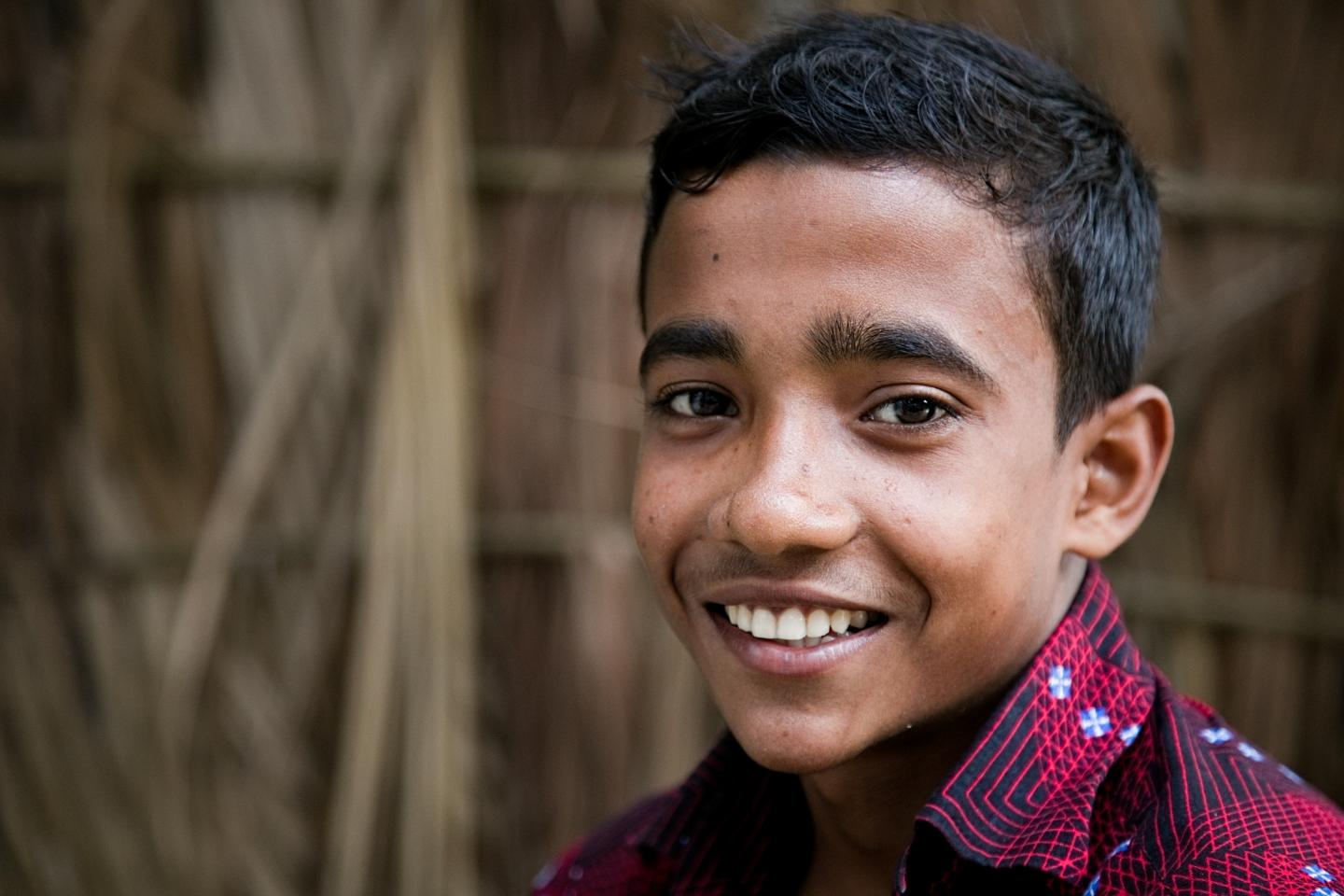 Mahadi, an adolescent boy, smiles at the camera wearing a dark blue shirt striped with red lines.