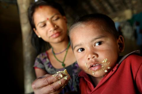 Mother feeds child rice and lentils