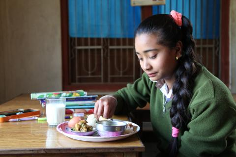 Young adolescent girl eating nutritious food in Nepal