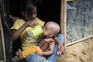 Rohingya refugee sips water from a mug held by her sister