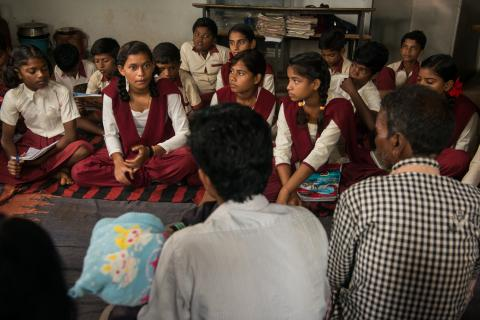 Kusma, surrounded by school girls in matching outfits, speaks to a group of men whose backs are to the camera. All are sitting.