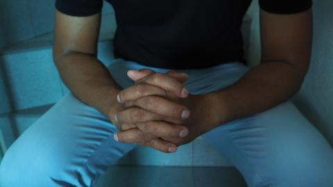 A shot of Ahmed sitting with his hands clasped, resting on his thighs. Only his torso and thighs are in the frame. He is wearing a black t-shirt with blue pants against a blue background.