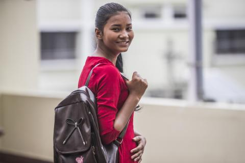 Nisha looks over her shoulder to smile at the camera, wearing a red shirt and leather backpack. Off-white buildings are in the background
