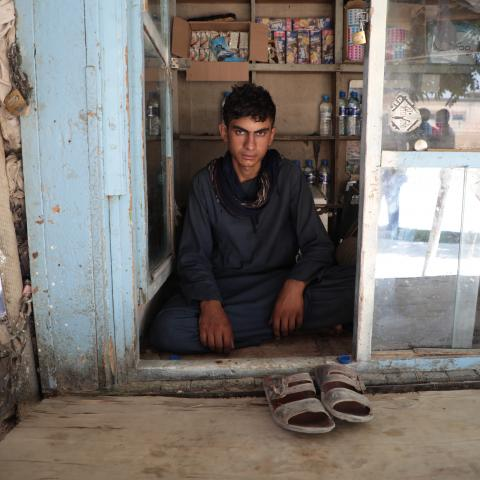 A teenage boy, Mujtaba, sits in the door of a small shop and looks at the camera with shop goods in the background.