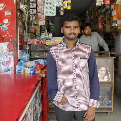 Ali looks at the camera with his shop of small goods in the background He is wearing a red-checkered button-up with blue sleeves.