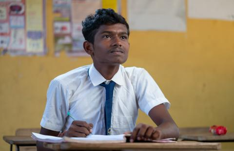 Inbarasa in his school uniform, a white button-up and blue tie, looks up while writing in his notebook. A blurred yellow classroom wall with posters is in the background.