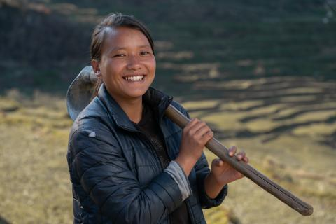 Kesang smiles at the camera wearing a blue down jacket with a spade slung over her shoulder.