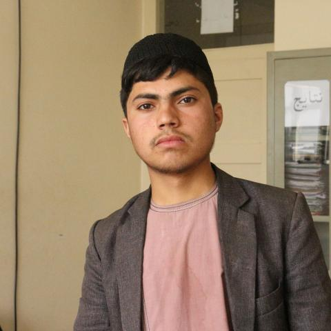 Naqibullah, an adolescent boy, looks at the camera with determination. He is wearing a black pakol, light red shirt and grey-brown sports jacket. A beige wall is in the background.