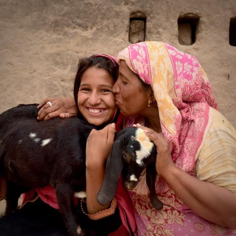 Farah beems while she holds a black goat and her mother kisses her on the cheek.