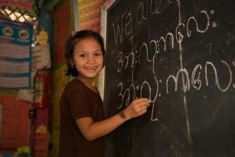A young girl writes on a chalkboard.