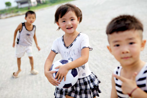 A small boy is in the foreground, a girl holding a soccer ball is in the mid-ground and another young boy is smiling in the background. All are on concrete pavement.