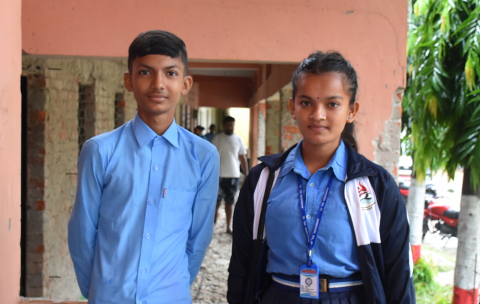 Pooja and Rakesh smile at the camera in their blue school uniforms.