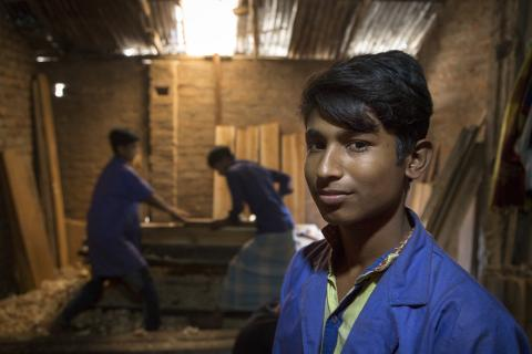 Adolescent boy smiles at the camera while two men work on wood in the background