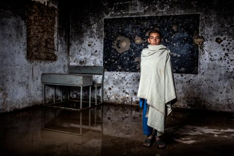 An adolescent boy looks starkly into the camera, standing in a classroom riddled with bullet holes in the concrete walls.