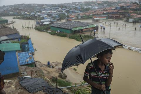 A young Rohingya boy in a t-shirt holds an umbrella while rain falls. In the background is Cox's Bazaar, flooded with brown water.