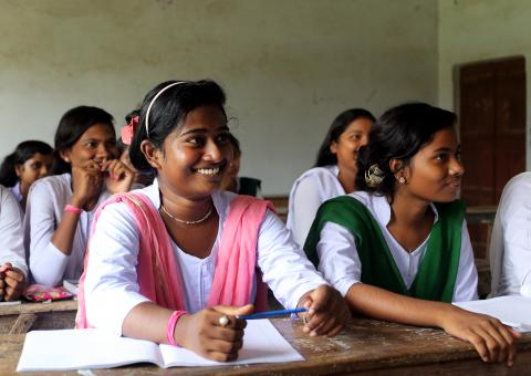 Adolescent girls smile away from the camera in a classroom, their books lay on their desks.