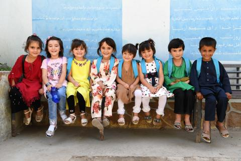 A group of young school children, wearing cyan-blue UNICEF backpacks, sit on a bench and look at the camera with wide smiles.