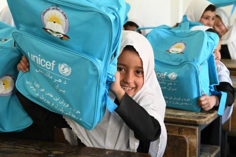 A young girl in a white hijab sits behind a desk and holds up a bright-blue UNICEF backpack, smiling