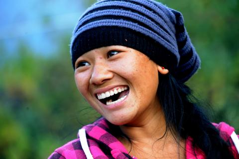 A girl wearing a stocking cap smiles away from the camera.