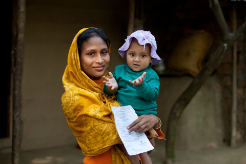 A young mother in a sari holds her child and their birth registration report.