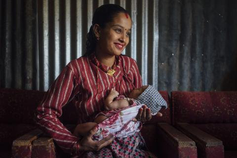 A young mother holds her newborn against her chest.