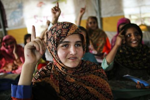 Zainab Jan (12) raises hand to answer the question asked by the teacher during her class in UNICEF-supported camp schools.