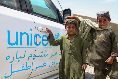 Two boys in Afghanistan standing in front of a UNICEF vehicle