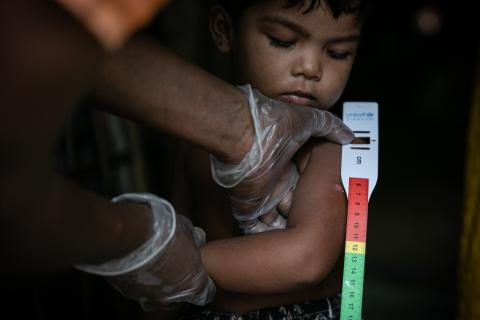 A Rohingya community volunteer measuring a child's mid-upper arm circumference to screen for malnutrition