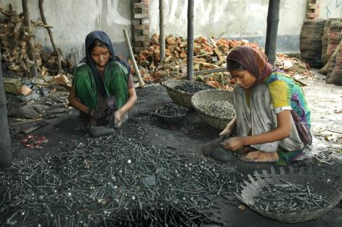 Two girls break used batteries to get pieces of metal out of them for recycling. They get between 40-60/day. Dhaka