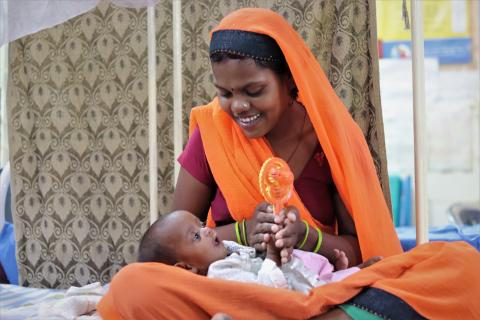 A young mother in a bright orange sari holds a toy over her underweight infant in her lap and smiles.