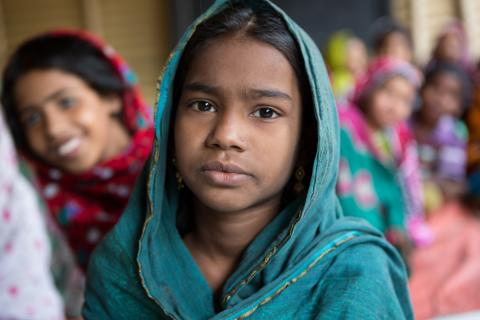 A girl from Bangladesh sits in her make-shift classroom