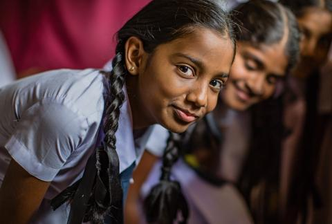 Yashasvi, in her blue school uniform, smirks at the camera with a classmate behind her.