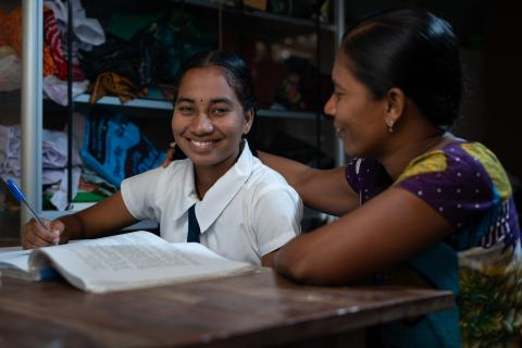 A young adolescent girl looks up from her textbook to smile at the camera, seated next to an older woman who appears to be assisting her with work.
