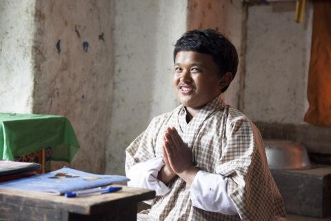 A Bhutanese boy with his hands together smiling at the camera