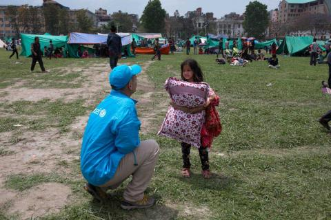 A girl stands holding a pillow talking to a UNICEF worker, field of tents in the background,