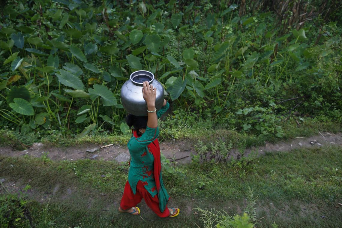 Manisha walks home with a pot of water she has collected at the community tap near her home.