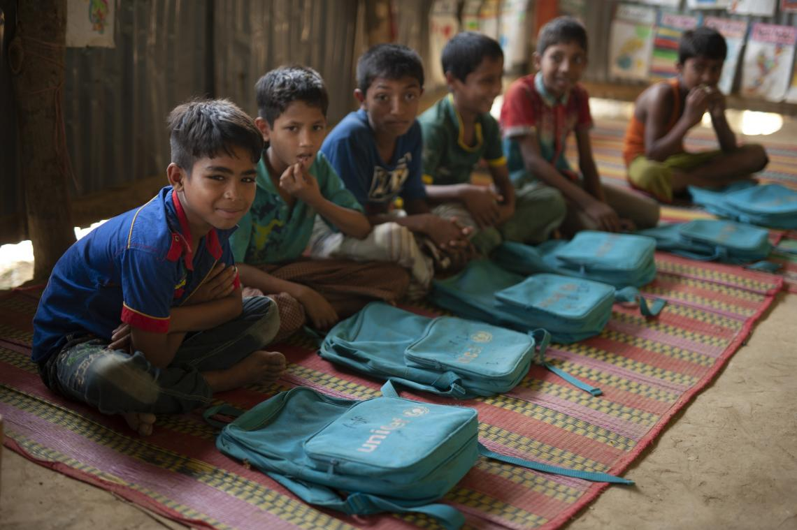 Young Rohingya boys sit in a line on a straw mat, cross-legged, and smile at the camera. Blue UNICEF backpacks are laying in front of each.