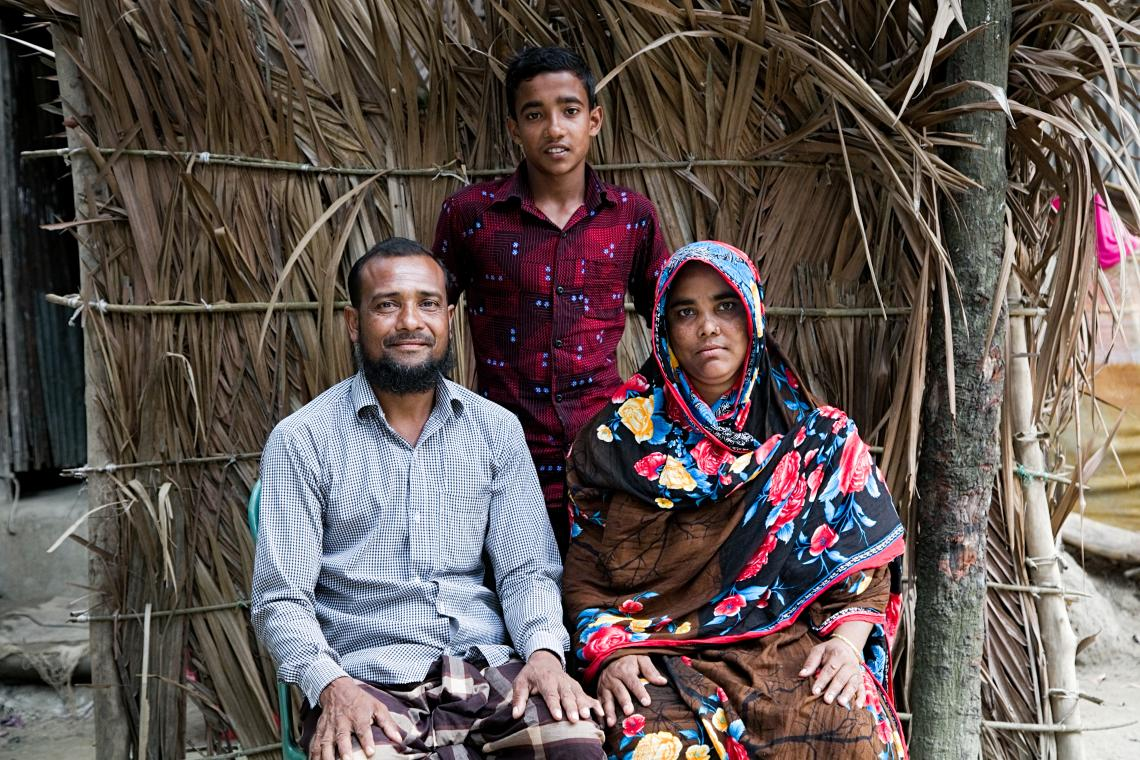 Mahadi stands behind his seated mother and father. In the background is a thatched wall.