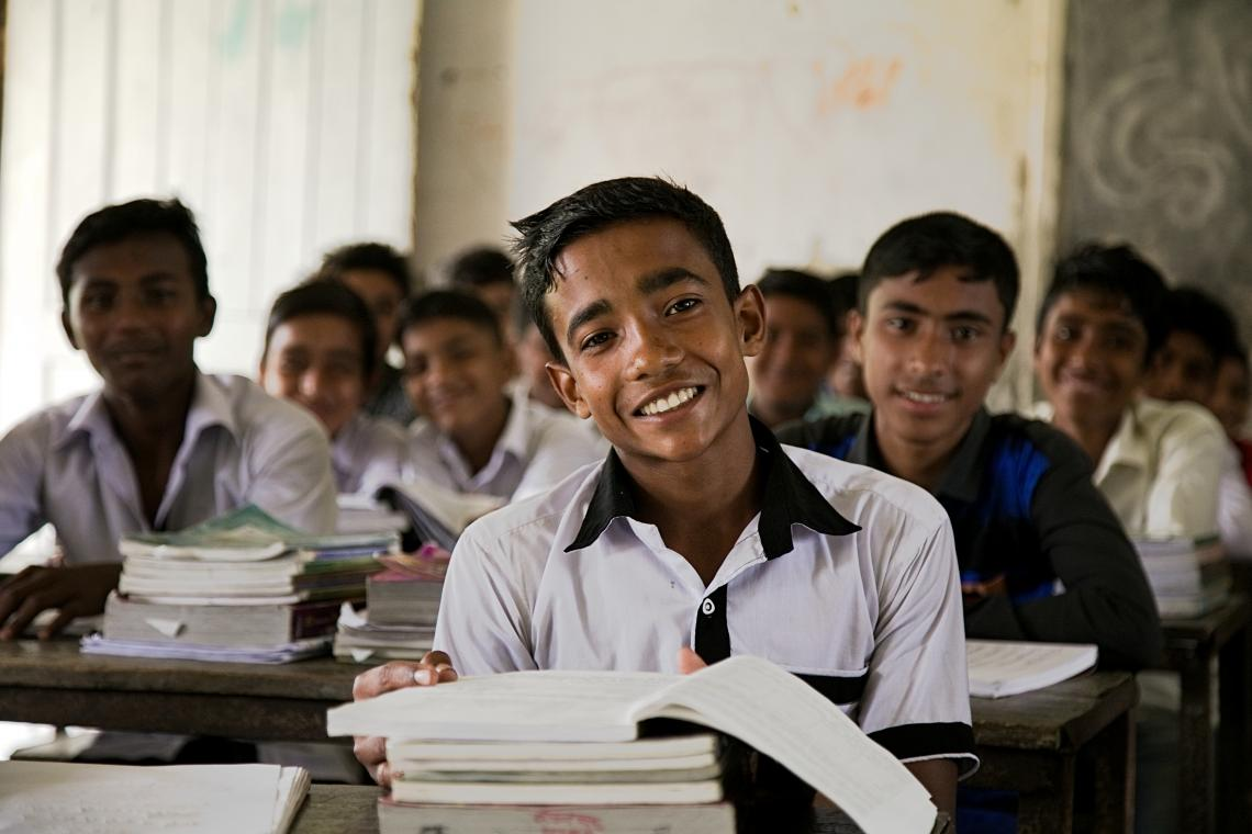 : Munadi smiles in class, a stack of textbooks is on his desk. Behind him are rows of smiling schoolboys.