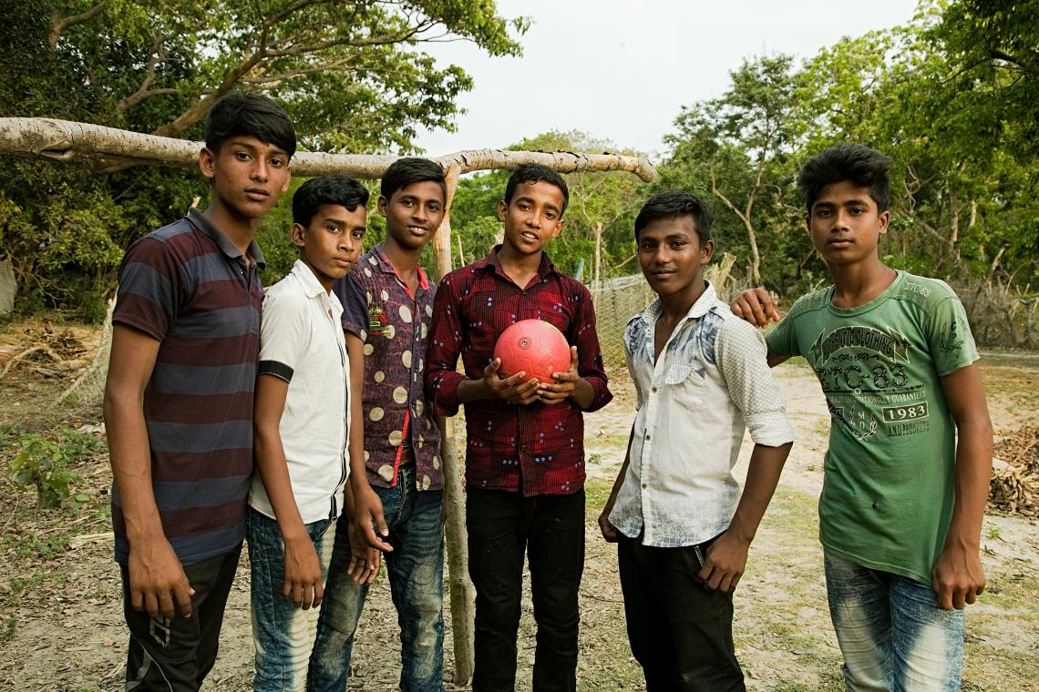 Mahadi stands holding a pink soccer ball, flanked by two boys his age on his left and three boys on his right. All are looking at the camera confidently and in the background is a cleared area, then forest.