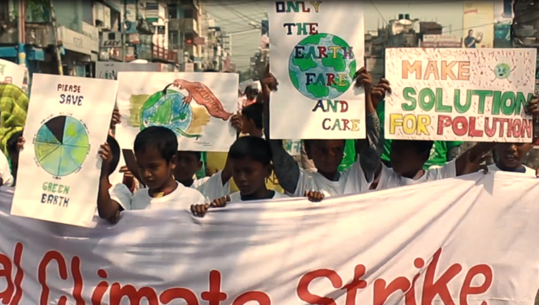 Young boys hold a banner and signs related to climate change in a demonstration.