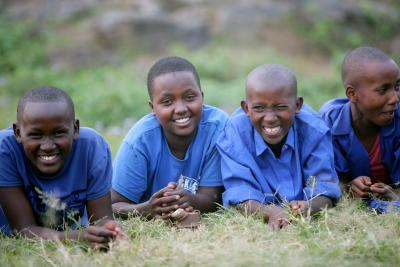 Four girls in Rwanda lay on the grass and smile at the camera