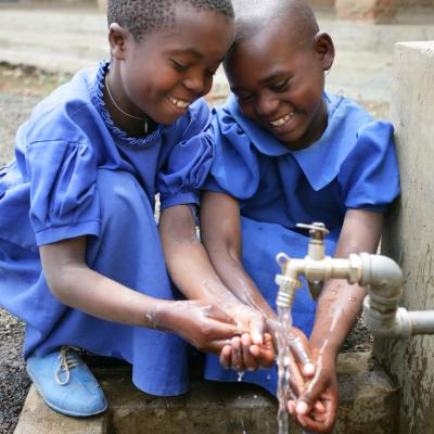 Two girls wash their hands with clean water from a tap