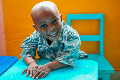 Young boy smiles and sits at a desk in pre-primary school